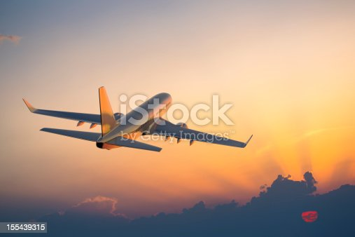 155439315istockphoto Passenger airplane flying above clouds during sunset 155439315