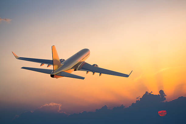 Passenger airplane flying above clouds during sunset Passanger airplane flying above clouds in evening. mid air stock pictures, royalty-free photos & images