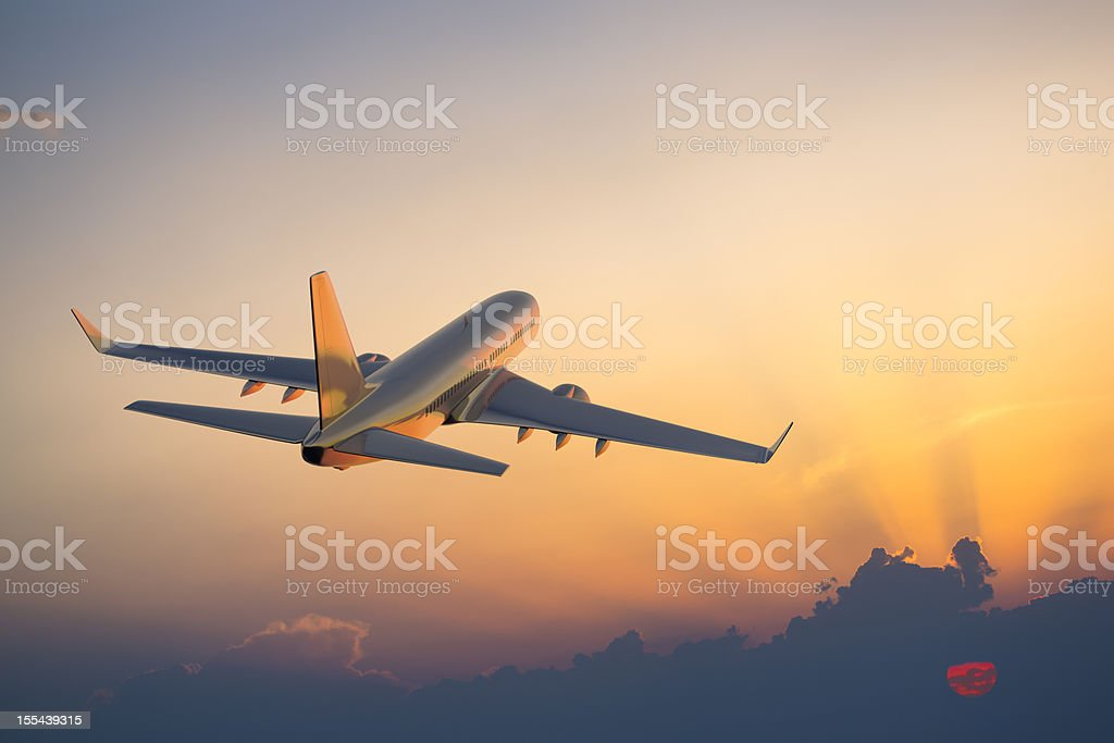 Passenger airplane flying above clouds during sunset stock photo