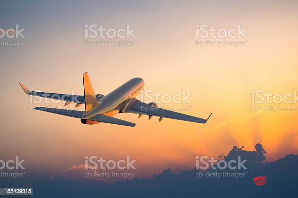 Photo of Passenger airplane flying above clouds during sunset