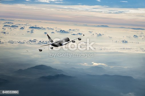 155439315istockphoto Passenger airplane flying above clouds during sunset 648333860