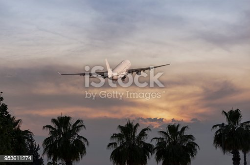 155439315istockphoto Passenger airplane flying above clouds during sunset 953611274