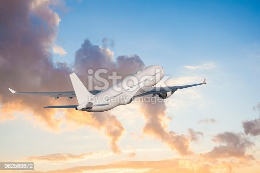 155439315istockphoto Passenger airplane flying above clouds during sunset 962589872