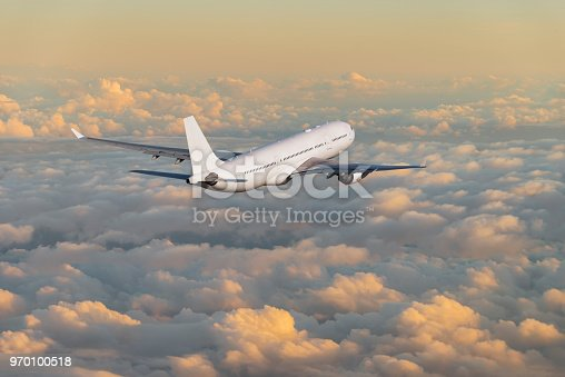 155439315istockphoto Passenger airplane flying above clouds during sunset 970100518