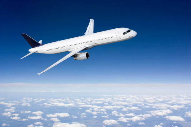 Passenger airplane flying above clouds stock photo