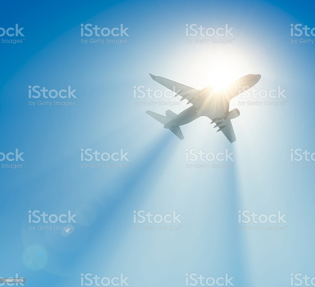 Passenger airplane flying against the sun royalty-free stock photo