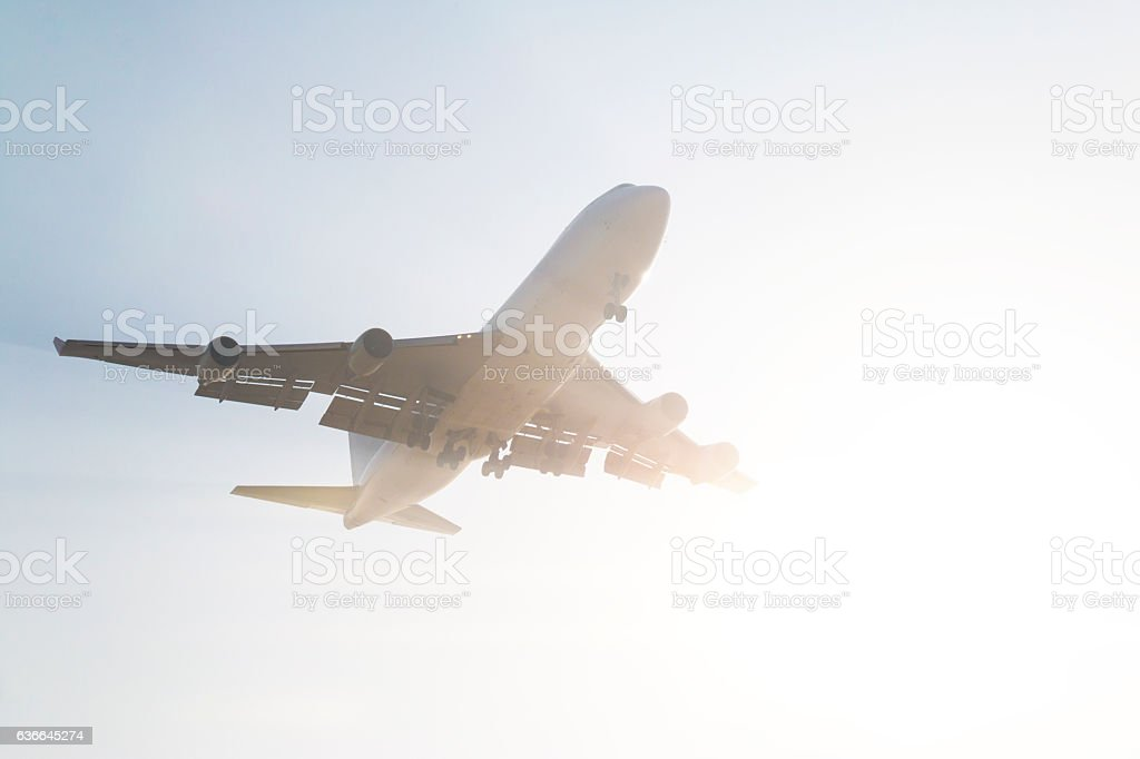 Passenger airplane flying against the sun stock photo