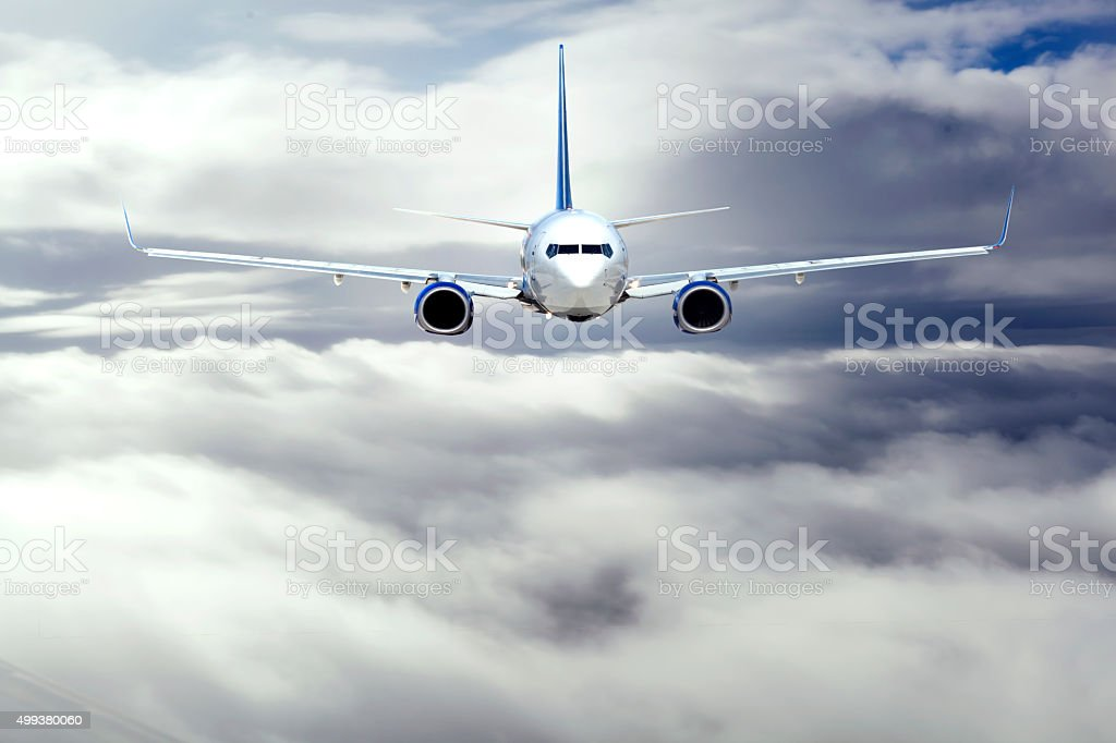 Passenger airplane flying high over the clouds stock photo
