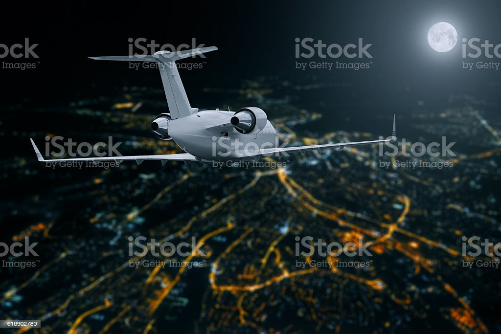 Passenger airplane flying over city at moon night stock photo