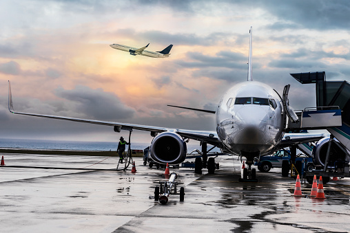 Passenger airplane being refueled and loaded with cargo before the flight near the terminal in an airport at the sunset .