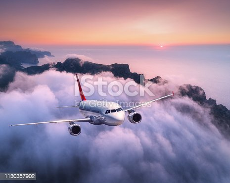 1058205304 istock photo Passenger airplane is flying over clouds at sunset. Landscape with white airplane, low clouds, sea coast, purple sky at dusk. Aircraft is landing. Business trip. Commercial plane. Travel. Aerial view 1130357902
