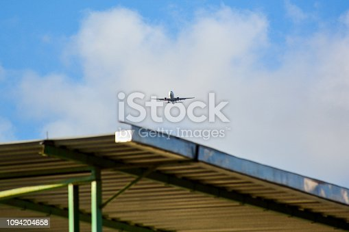 494996104istockphoto Passenger airplane landing against blue cloudy sky 1094204658