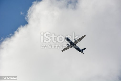 494996104istockphoto Passenger airplane landing against blue cloudy sky 1094205202