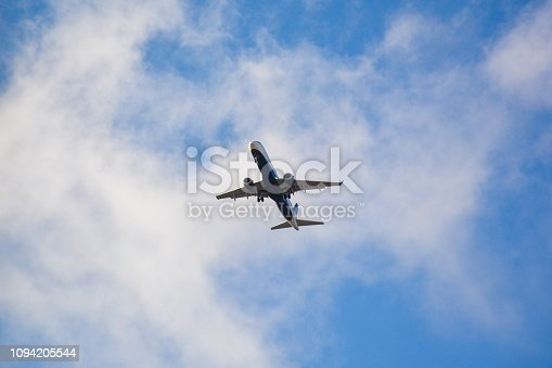 494996104istockphoto Passenger airplane landing against blue cloudy sky 1094205544