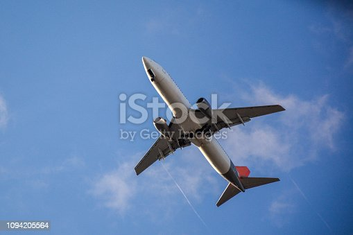 494996104istockphoto Passenger airplane landing against blue cloudy sky 1094205564
