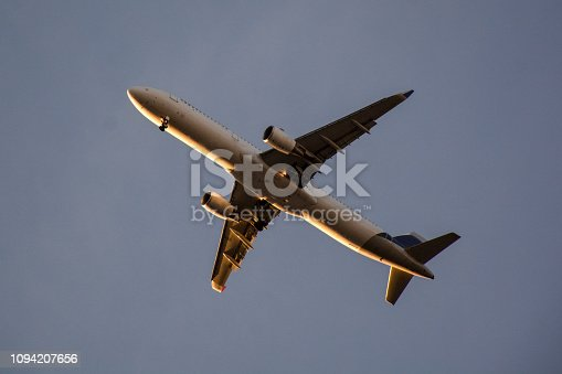 494996104istockphoto Passenger airplane landing against blue cloudy sky 1094207656