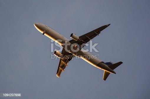 494996104 istock photo Passenger airplane landing against blue cloudy sky 1094207656