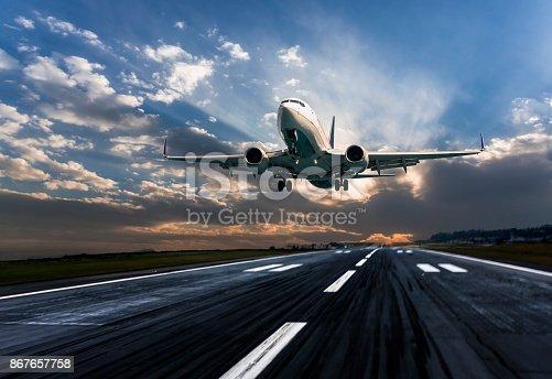 istock Passenger airplane landing at dusk 867657758