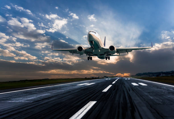 passenger airplane landing at dusk - flying stock photos and pictures