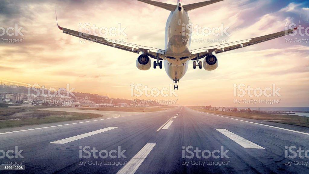 Passenger airplane landing at sunset stock photo