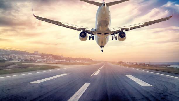 pasajeros de avión aterrizando en puesta de sol - aterrizar fotografías e imágenes de stock