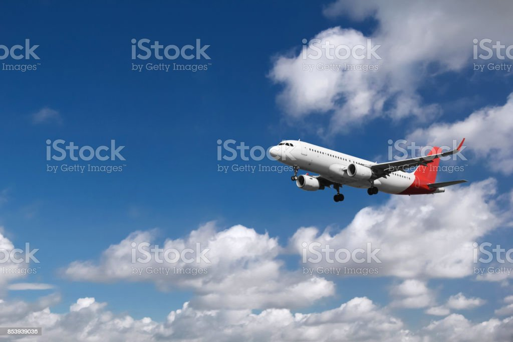 Passenger airplane landing with clouds in the background stock photo