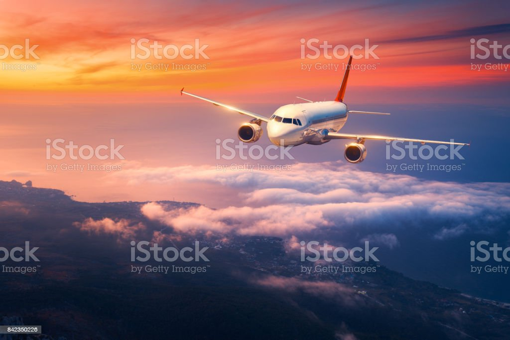 Passenger airplane. Landscape with big white airplane is flying in the sky over the clouds and sea at colorful sunset. Passenger aircraft is landing at dusk. Business trip. Commercial plane. Travel stock photo