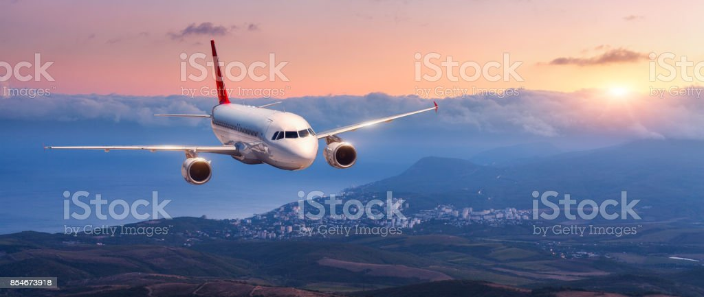 Passenger airplane. Landscape with white airplane is flying in the orange sky with clouds over mountains, sea at colorful sunset. Passenger aircraft is landing. Commercial plane. Private jet. Travel stock photo