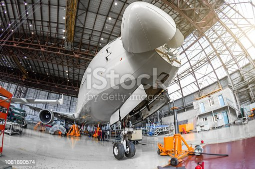 Passenger airplane on maintenance of engine and fuselage check repair in airport hangar. With an open hood on the nose under the cockpit of pilots