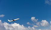 Commercial aircraft landing or taking off from the airport with blue cloudy sky in the background