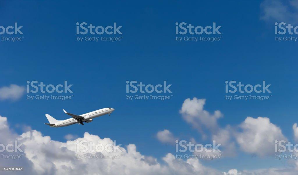 Avião de passageiros sobre o fundo de céu azul e nuvens brancas, pousando no aeroporto. - foto de acervo