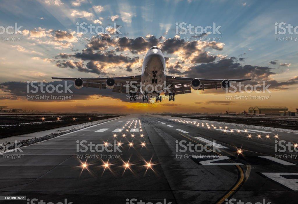 Passenger airplane taking off at sunset stock photo