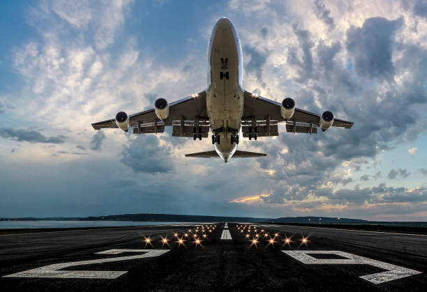 avión de pasajeros despeando al atardecer - avión fotografías e imágenes de stock