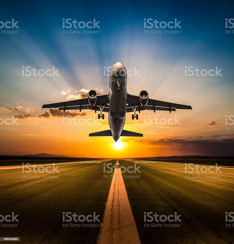 Passenger airplane taking off at sunset stock photo