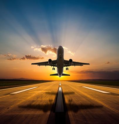 Passenger jet airplane taking off at sunset