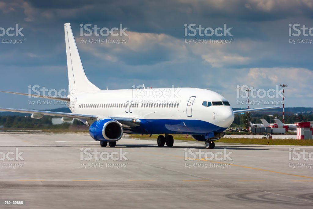Passenger airplane taxiing on the main taxiway stock photo