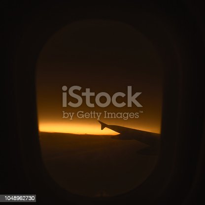istock Passenger airplane.  View from airplane window on the wing during  sunset over the clouds. Business trip. Travel concept