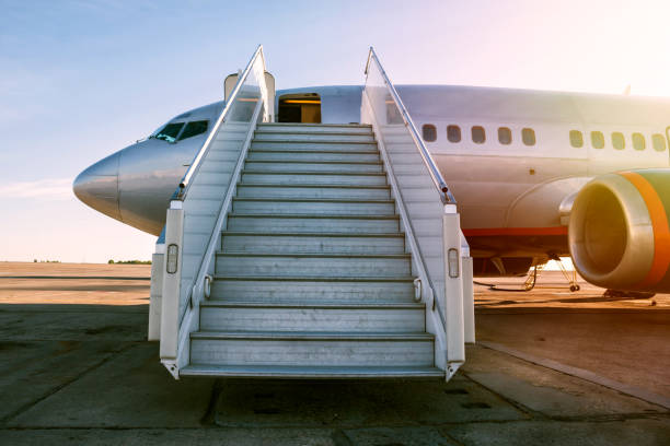 Passenger airplane with a boarding steps in the morning sun stock photo