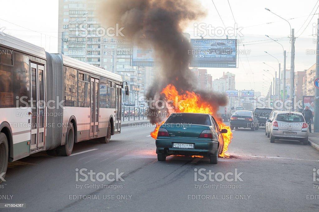 Passenger bus passing near burning car stock photo