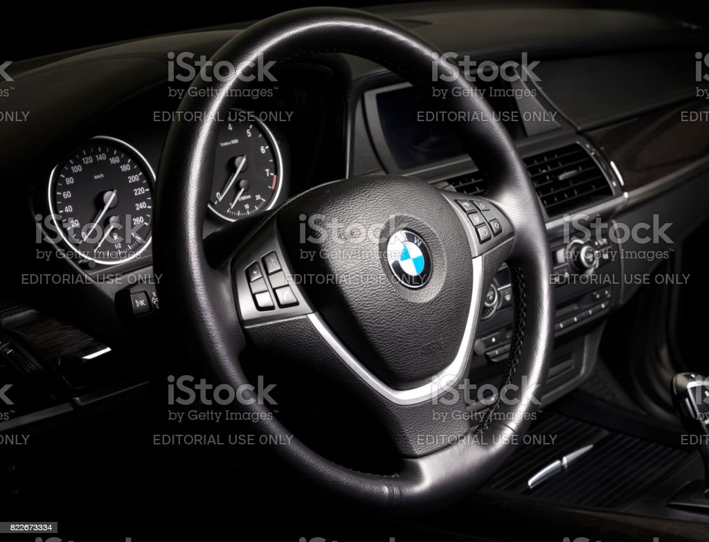 BMW passenger car interior showing steering wheel and gear shift  in black leather interior стоковое фото