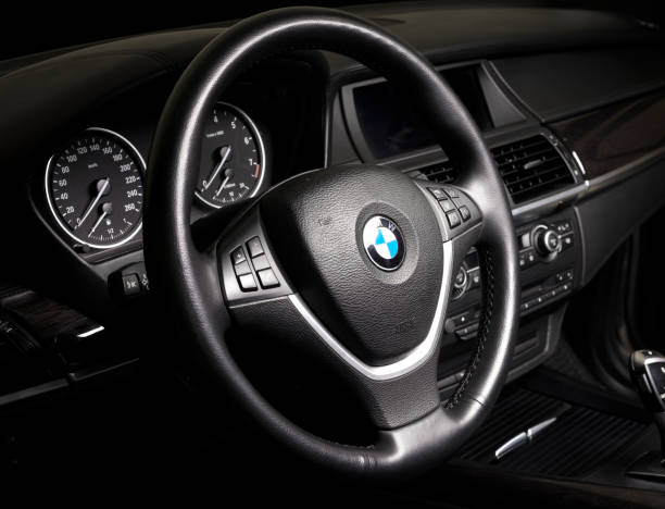 BMW passenger car interior showing steering wheel and gear shift  in black leather interior stock photo