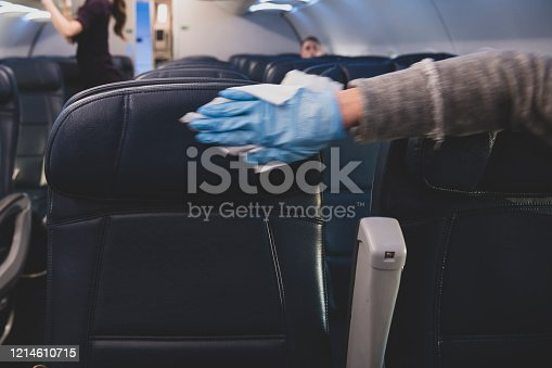 A passenger who has just boarded an airplane wears a plastic glove while using a wipe to disinfect the airplane seats and armrests on her row.