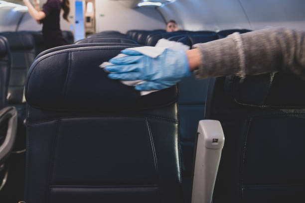 Passenger disinfecting airplane seats after boarding flight stock photo