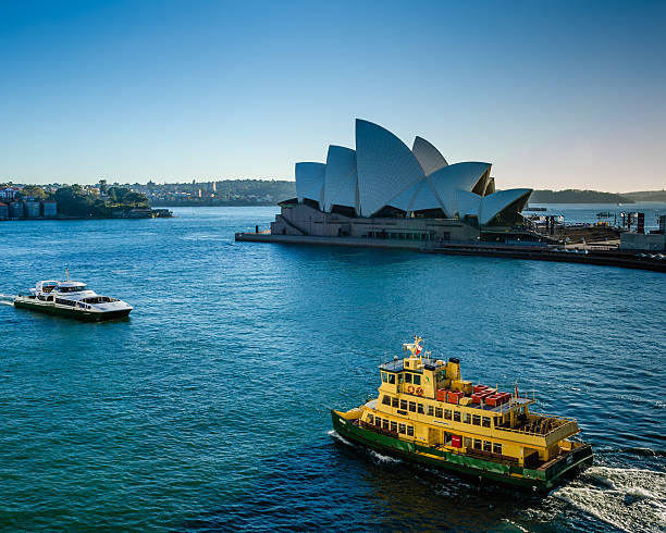 Passenger ferries sail past the Sidney Opera House stock photo