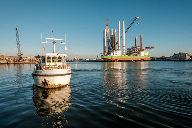 "Passenger ferry in the port of Ostend in Belgium Passenger ferry in the port of Ostend with in the background the mighty wind turbine installation vessel ""u2018Sea Installer""u2019, Thursday 2 August 2018, Ostend, Belgium verbinding stock pictures, royalty-free photos & images"
