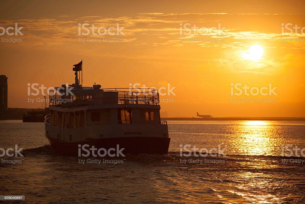 Passenger ferry leaving Boston harbor at sunrise. stock photo