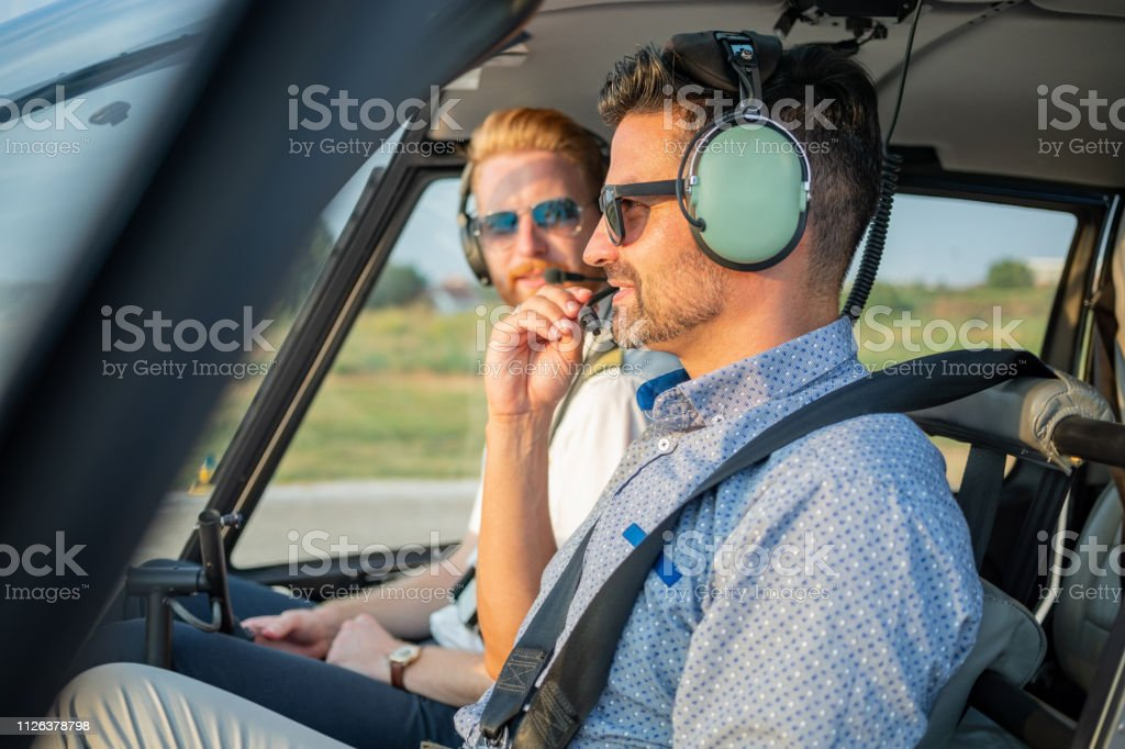 Passenger sitting with pilot in helicopter cockpit holding and...