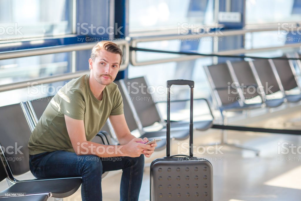 Man passenger in an airport lounge waiting for flight aircraft. Young...