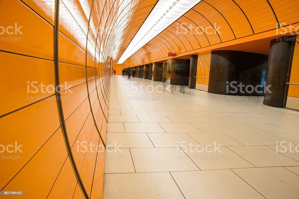 Passenger in an orange subway passage stock photo