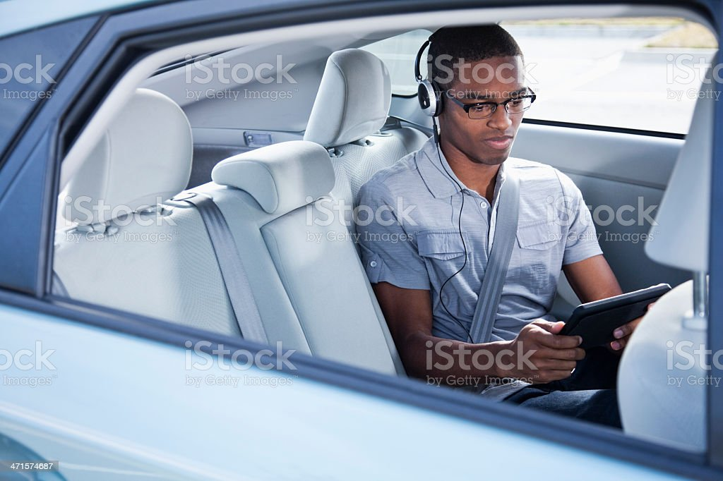 Passenger in car using digital tablet stock photo